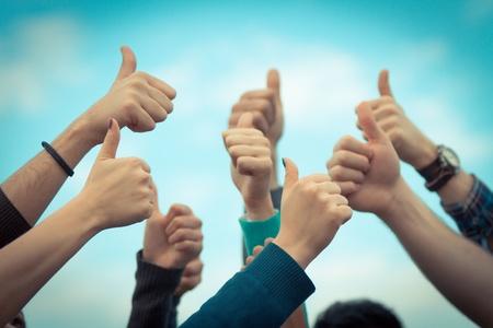 Los estudiantes universitarios con los pulgares arriba