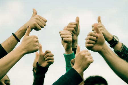 manos levantadas: Estudiantes universitarios con los pulgares arriba