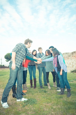 Multiracial Students with Hands on Stack photo