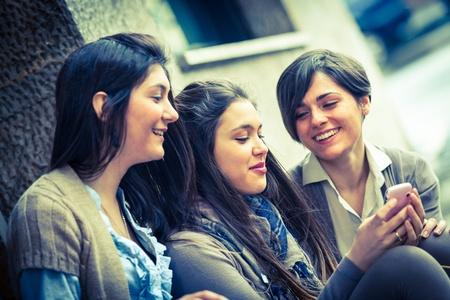 amigas conversando: Grupo de Mujeres de envío de mensajes con el teléfono móvil