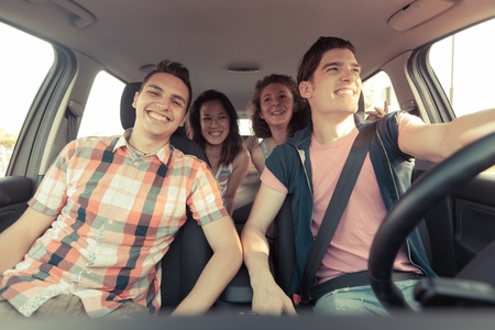 car driving: Four Friends in a Car Leaving For Vacation Stock Photo