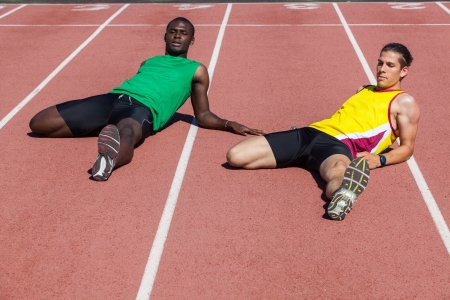 Two Track and Field Athletes Stretching Stock Photo - 14065077