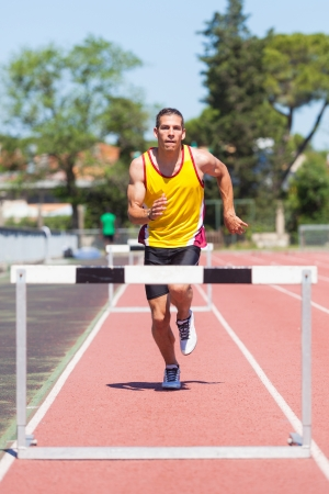 obstacle course: Male Track and Field Athlete during Obstacle Race Stock Photo