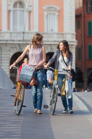 city bike: Two Beautiful Women Walking in the City with Bicycles and Bags