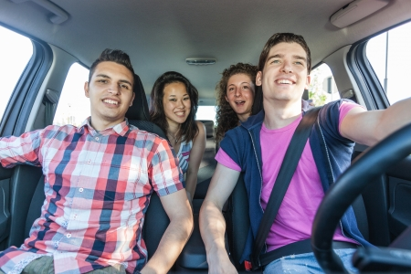 woman driving car: Four Friends in a Car Leaving For Vacation Stock Photo