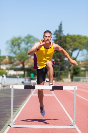hurdle: Male Track and Field Athlete during Obstacle Race Stock Photo