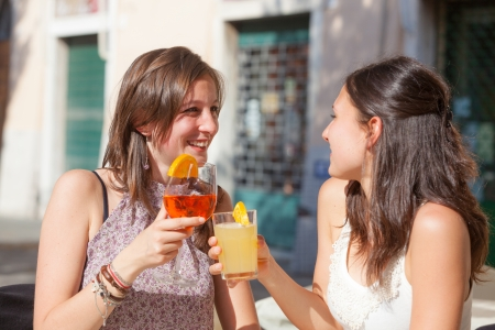 Two Young Women Cheering with Cold Drinks photo