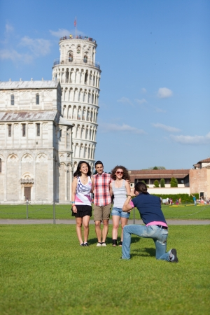 Group of Friends Taking Photo with Pisa Leaning Tower on Background photo