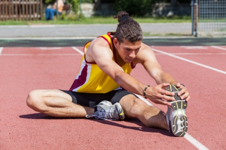 atletismo: Track and Field Athlete Stretching Foto de archivo