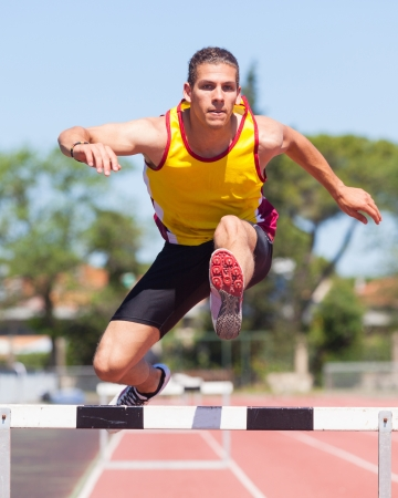 track: Male Track and Field Athlete during Obstacle Race Stock Photo