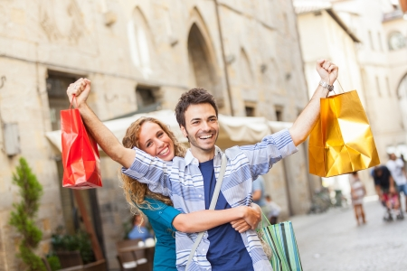 man and woman with shopping bags: Happy Young Couple with Shopping Bags Stock Photo
