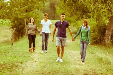 teenagers laughing: Group of Teenagers Walking Holding Hands Stock Photo