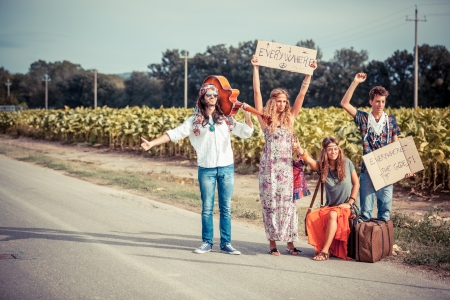 hitchhiking: Hippie Group Hitchhiking on a Countryside Road