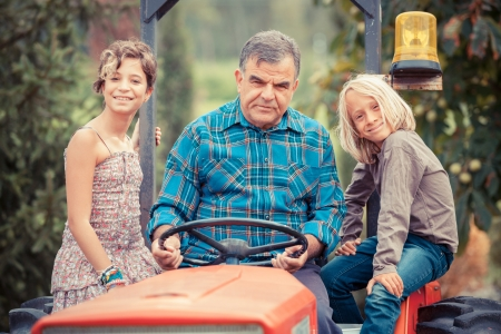 Adult Farmer with Children on Tractor photo
