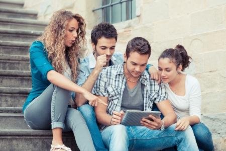 Groep vrienden met Tablet PC Stockfoto