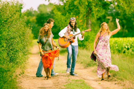 hippy: Hippie Group Playing Music and Dancing Outside Stock Photo