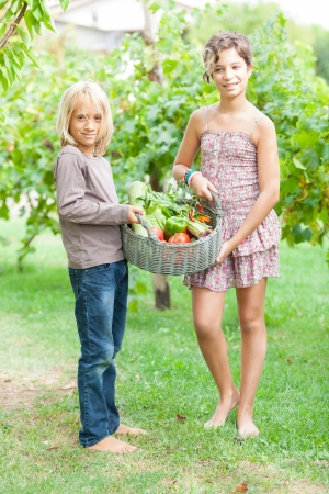 Boy and Girl Holding Basket of Vegetables photo