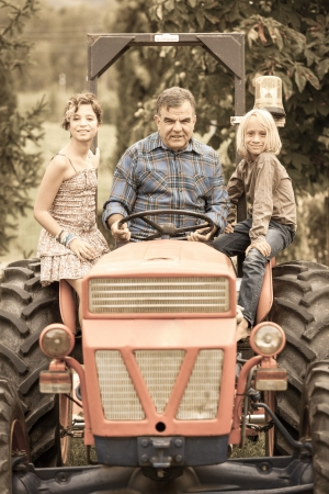 Adult Farmer with Children on Tractor Stock Photo - 15391984