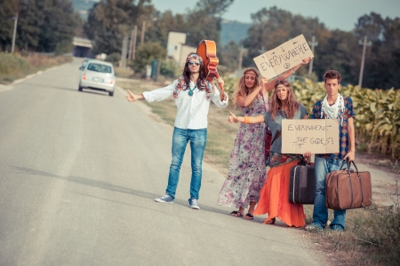 Hippie Group Hitchhiking on a Countryside Road photo