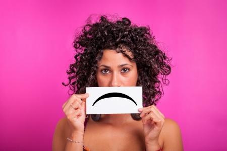 mirada triste: Mujer joven con Emoticon triste sobre fondo fucsia Foto de archivo