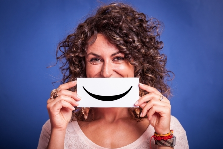 Young Woman with Smiley Emoticon on Blue Background photo