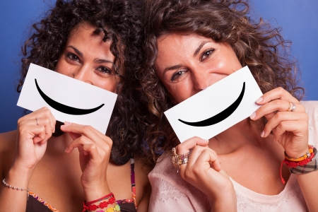smiley face icon: Two Young Women with Smiley Emoticon on Blue Background