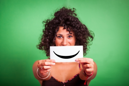 Young Woman with Smiley Emoticon on Green Background photo