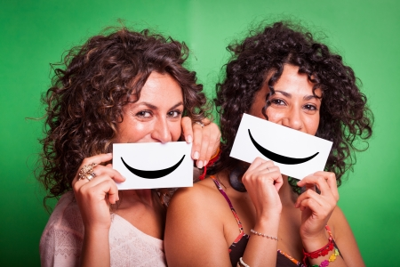 Two Young Women with Smiley Emoticon on Green Background Stock Photo - 15404572