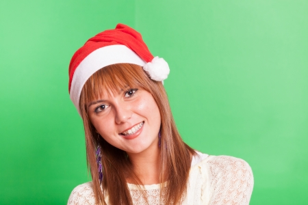 Cheerful Woman with Santa Hat on Green Background photo