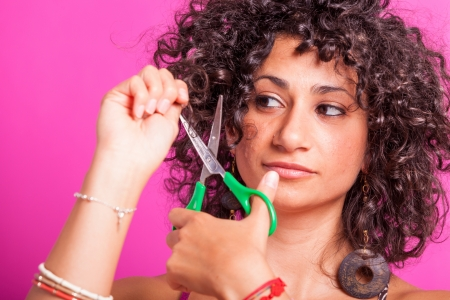 Young Woman Cutting her Curly Hairs photo