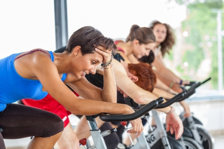 tired person: Group of People Cycling at Gym
