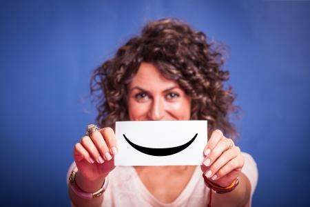 cara sonriente: Mujer joven con Smiley Emoticon sobre fondo azul