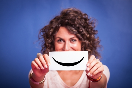 smiley face: Young Woman with Smiley Emoticon on Blue Background