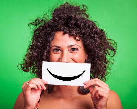 felicidad: Mujer joven con Smiley Emoticon sobre fondo verde