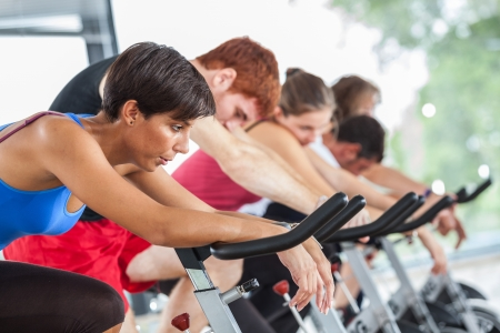 tired man: Group of People Cycling at Gym