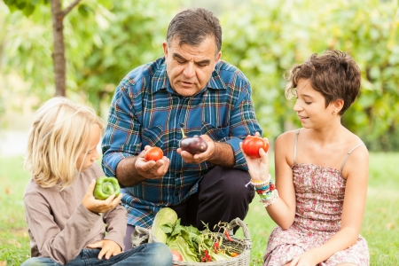 Adult Farmer with Children and Harvested Vegetables photo