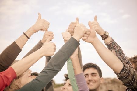 manos levantadas: Los estudiantes universitarios con los pulgares para arriba