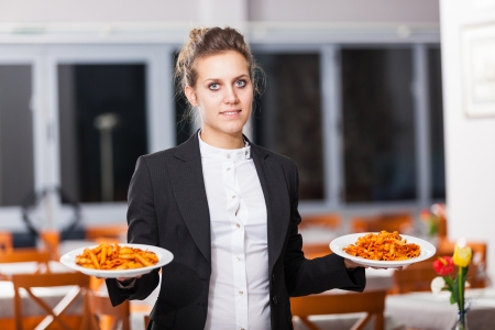 Waitress in the Restaurant Holding Dishes photo