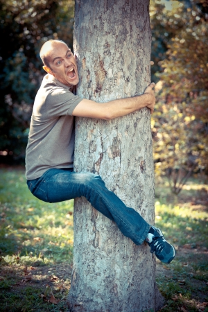 clinging: Funny Man Clinging to a Tree Stock Photo