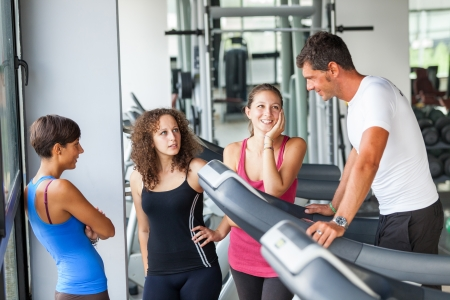 playboy: Attractive Man at Gym with Three Women Stock Photo