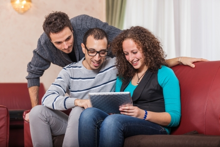 Three Friends with Tablet PC on a Sofa photo