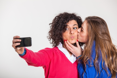 Two Beautiful Women Taking Self Portrait with Mobile Phone photo