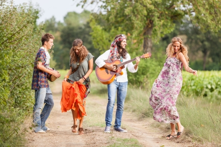 women hips: Hippie Group Playing Music and Dancing Outside Stock Photo
