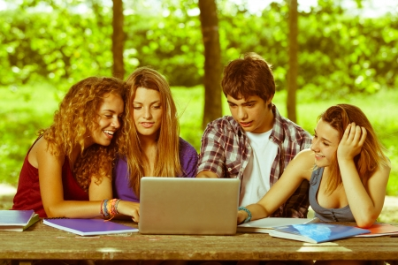 Group of Teenage Students at Park with Computer and Books photo
