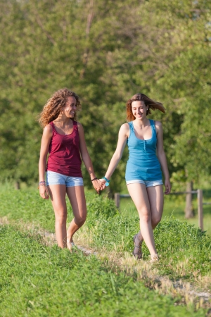 Two Beautiful Teenage Girls Walking at Park photo