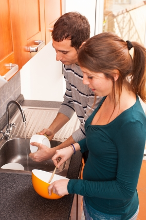 Wife Cooking While Husband Washing Dishes photo
