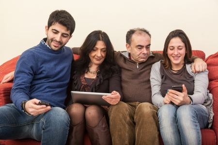 Happy Family on the Sofa with Electonic Devices photo