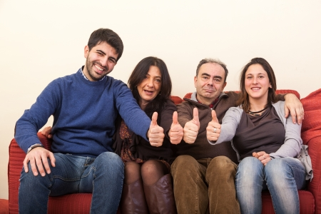 Happy Family on the Sofa with Thumbs Up photo