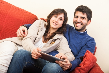 Young Couple on the Sofa with Tablet PC Stock Photo - 17540400