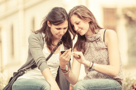 Two Beautiful Women Sending Messages with Mobile photo